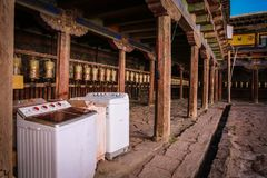 Tibetan monastary equipped with washing machines. Right to the side of the prayer mills in the interior of a tibetan monastary several washing machines are Stock Photo