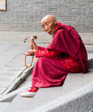 Tibetan Monk. A monk on the steps, left hand holding a rosary, his right hand holding a prayer wheel Stock Photo