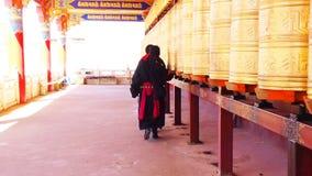 Tibetan monk and nun walking and spinning the prayer wheels in Yarchen Gar Monastery stock video footage