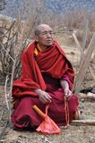 Tibetan Monk. A Tibetan monk sits outside waiting for his friends in China Stock Photo