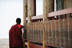 A tibetan monk turning prayer wheels Stock Images