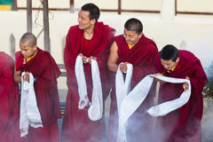 Tibetan monks bowing with frankincense smoke for welcoming high level monk in area of Rumtek Monastery near Gangtok. Sikkim, India Royalty Free Stock Image