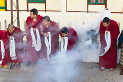 Tibetan monks bowing with frankincense smoke for welcoming high level monk in area of Rumtek Monastery near Gangtok. Sikkim, India Stock Image