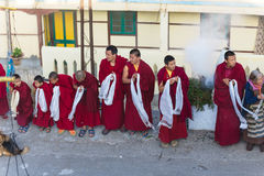 Tibetan monks bowing with frankincense smoke for welcoming high level monk in area of Rumtek Monastery near Gangtok. Sikkim, India Royalty Free Stock Photo