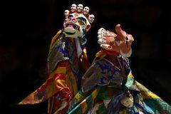 Tibetan monks in carnival costumes perform ancient sacred dance Mask in ritual bright clothes. Stock Photos