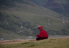 Tibetan monks sitting on the hill royalty free stock image
