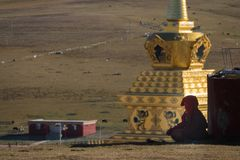 A Tibetan monks sitting on the hill at sunlight in Yarchen Gar. A Tibetan monks sitting on the hill at sunlight in Yarchen Gar, Sichuan, China. Yarchen Gar is Stock Photography