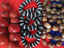 Tibetan national jewelry: large round beads of red coral, striped stones mascots, Buddhist stones defenders on red background. Tibetan national jewelry: large Stock Photo