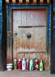 Tibetan oil flasks. Oil flasks and a potty in front of an old wooden door in a buddhist temple in Lhasa,Tibet Royalty Free Stock Photos