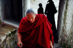 Tibetan old lama. He is a Tibetan buddhist believers, the lama dressed in red.Because the older, up the steps of panting, legs and feet dont convenient, walk Royalty Free Stock Photo