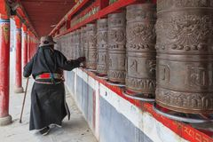 Tibetan people spinning the prayer wheels around Mani Temple Mani Shicheng a famous landmark in the Tibetan city of Yushu Jyekundo Royalty Free Stock Photography