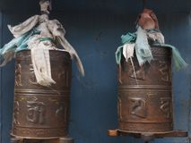 Tibetan prayer drums, metal barrels with prayers in Sanskrit against blue wall background. Royalty Free Stock Photos
