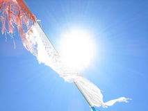 Tibetan prayer flags. Details of Tibetan prayer flags with blue sky and sun Stock Images
