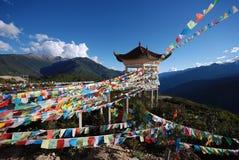 Tibetan Prayer Flags. Colourful Tibetan prayer flags surround a prayer tower in a Tibetan village in Shangri La in Yunnan Province, China Stock Photos