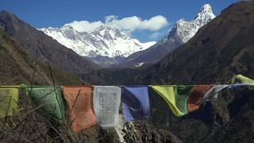 Tibetan prayer flags against white snowy mountain peak in the Everest region of Himalayan mountains, Nepal.  stock video