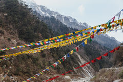 Tibetan prayer flags with Black mountain with snow on the top is background at Thangu and Chopta valley in winter in Lachen. Stock Photos