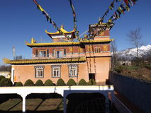 Tibetan prayer flags. A house made of rocks with sun shining brightly on one side Royalty Free Stock Photos