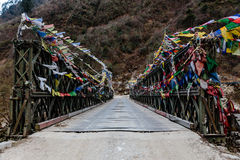 Tibetan prayer flags swaddled with bridge over frozen river with Black mountain with snow on the top is background at Thangu. Royalty Free Stock Photography