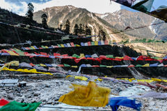 Tibetan prayer flags waving and swaddled with trees an mountain in sideway over frozen river with mountain in background. Stock Photos