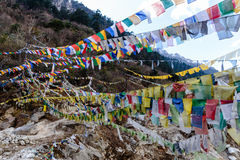 Tibetan prayer flags waving and swaddled with trees an mountain in sideway over frozen river at Thangu and Chopta valley in winter Stock Photo