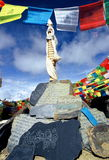 Tibetan Prayer Stones & flags. Mani stone carving is a time-honored and unique way that Tibetan people record and carry forward their culture. Wherever you go in Stock Photo