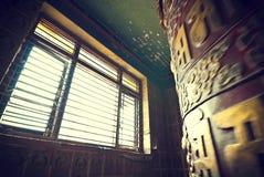 Tibetan prayer wheel. Lit by open window Stock Photography