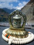 Tibetan Prayer Wheel in Car. A Tibetan prayer wheel in the windshield of a car. The car is driving along a mountainous road in western China royalty free stock images