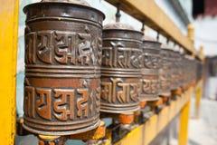 Tibetan prayer wheels or prayers rolls of the faithful Buddhists. Horizontal. Closeup photo. Stock Photo