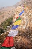 Tibetan prayful flags, over the Mahakala`s cave. Lungta horse of wind - the Tibetan prayful flags, over a mountain ridge with Mahakala`s cave, the place where royalty free stock photo