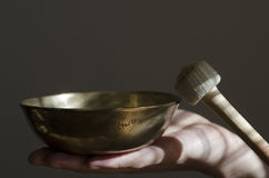 A Tibetan singing bowl being played with a baton. A Tibetan singing bowl sitting in a hand being played with a baton Stock Images