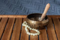 Tibetan singing bowl and jade beads on a wooden stand royalty free stock images