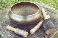 Tibetan Singing  bowl with mallets on a wooden backgroung. Asian traditional theme. Photo with color toning Stock Photo