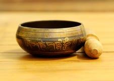 Tibetan singing bowl resting on a teak wood table. Royalty Free Stock Photography