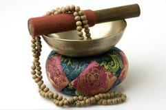 Tibetan Singing Bowl with sandalwood prayer beads. Tibetan singing bowl on quilted stand with sandalwood prayer beads Stock Photo