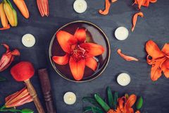 Free Tibetan Singing Bowl With Floating In Water Lily Inside. Special Sticks, Burning Candles, Lily Flowers And Petals On The Black Woo Stock Image - 106416991