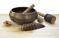 Tibetan singing bowl on a wood table. Traditional asian music bowl with wooden mallets and feather Royalty Free Stock Photos
