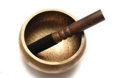 A Tibetan singing bowl with a wooden striker. A photo taken on a Tibetan singing bowl with a single wooden striker partially wrapped in black velvet cloth royalty free stock image
