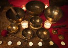 Tibetan singing bowls. Studio shot of Tibetan singing bowls with burning candles Stock Photos