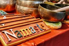 Tibetan singing bowls and wooden Namaste traditional greeting signs. On sale in oriental fair Turin Italy March 23 2018 royalty free stock photos