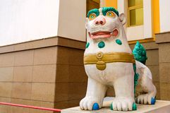 Tibetan snow lion with turquoise mane in front of entrance to Buddhist temple. Symbol of snow Himalayan mountains and sky.  royalty free stock images