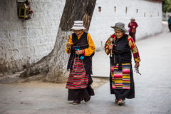 Tibetan Streetsnap in Potala Palace. A couple of Tibetan prayers who are chatting and  turning her prayer wheel Stock Image