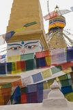 Tibetan stupa with the face and eyes of Buddha and golden peak among the different colors of prayer flags, vertical photography, K Royalty Free Stock Photos
