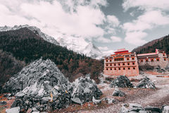 Tibetan temple on the snow mountain with gray rocks in Yading Nature Reserve, China. Stock Images