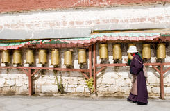 Tibetan turns pray wheel Stock Image