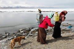 Tibetan vrouwen die water halen Stock Afbeeldingen