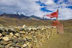 Tibetan wall of stone. With red flag Stock Photo