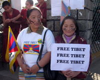 Tibetan Women Uprising Day Dharamsala India. A Tibetan woman and her daughter sport face paint with slogans, signs demanding human rights and a Free Tibet, and Royalty Free Stock Photo