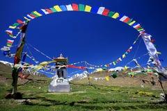 Tibetana buddistiska bönflaggor och stupa på fält för lös blomma in Arkivbilder