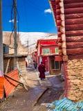 Tibetana buddistiska munkar som går i en nerrowgata på Yarchen, Gar Fotografering för Bildbyråer