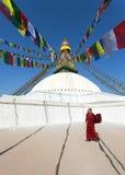 Tibetana buddistiska munkar som går runt om den Boudhanath stupaen under festival Royaltyfria Bilder